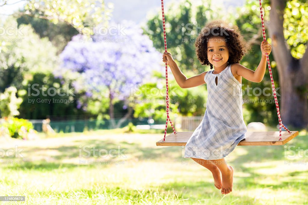 Smiling young girl on a swing in a park stock photo
