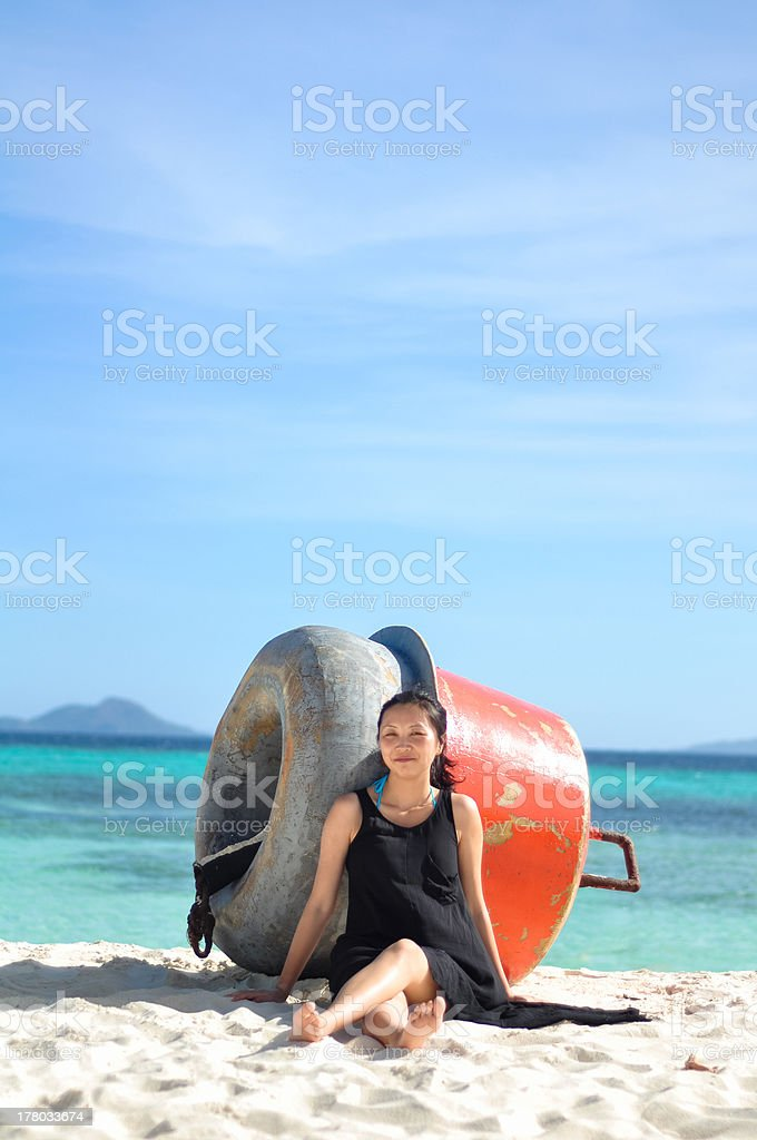 smiling young girl sits on white beach royalty-free stock photo