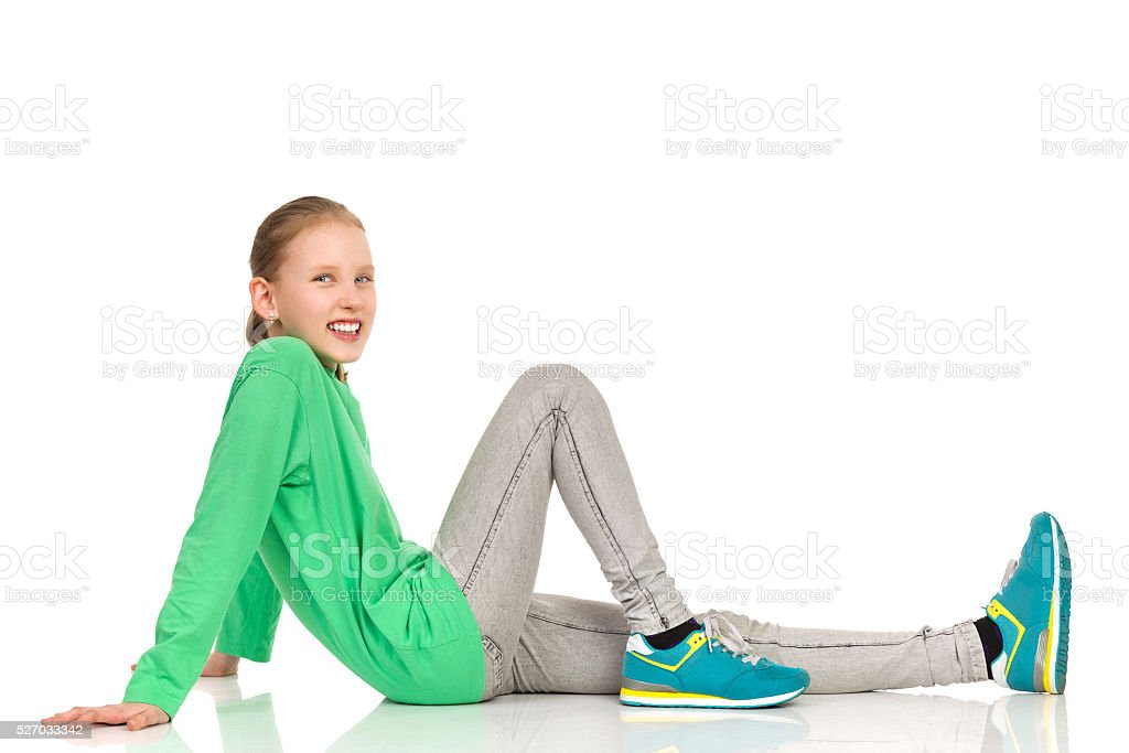 Smiling Young Girl Sitting On Floor stock photo