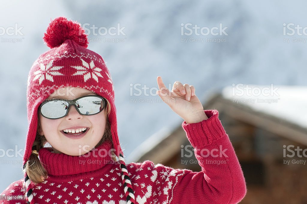 Smiling young girl wearing red outfit and sunglasses at snow stock photo