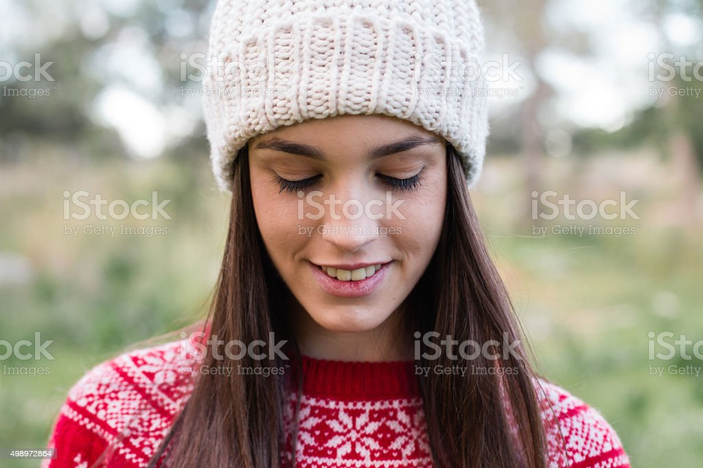 Smiling young girl wearing winter outfit looking down stock photo