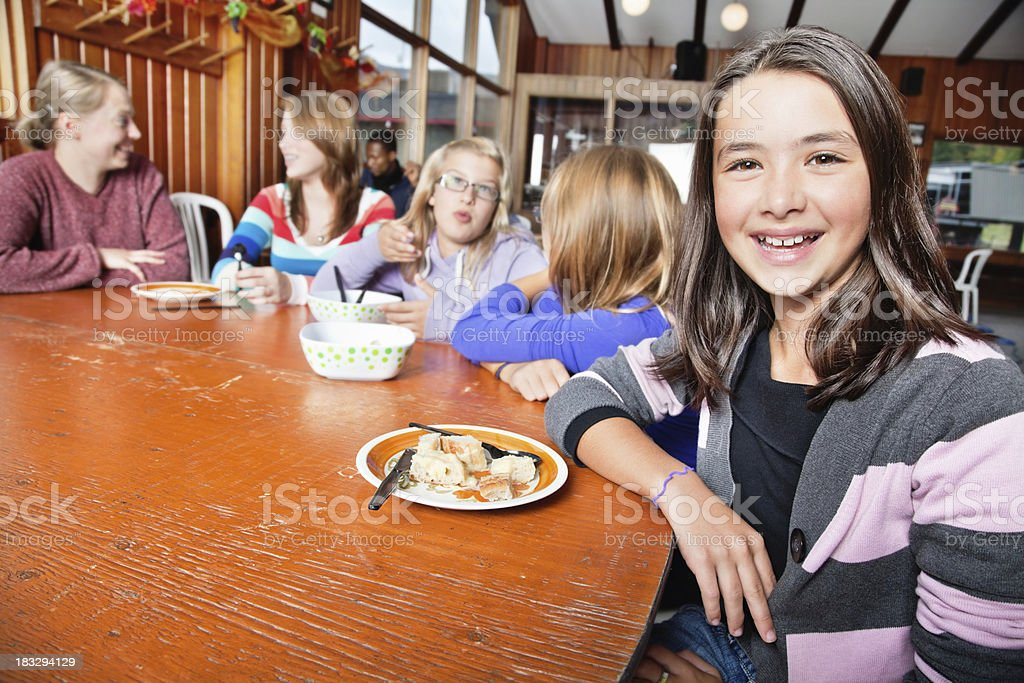 Smiling Young Girl With Friends in Cafeteria at Summer Camp royalty-free stock photo