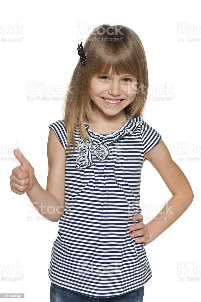 Smiling young girl with her thumb up stock photo
