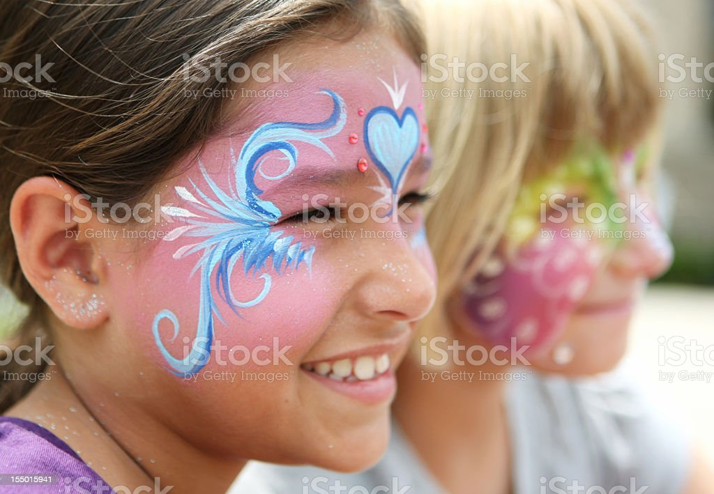 Smiling young girls wearing colorful face paint stock photo