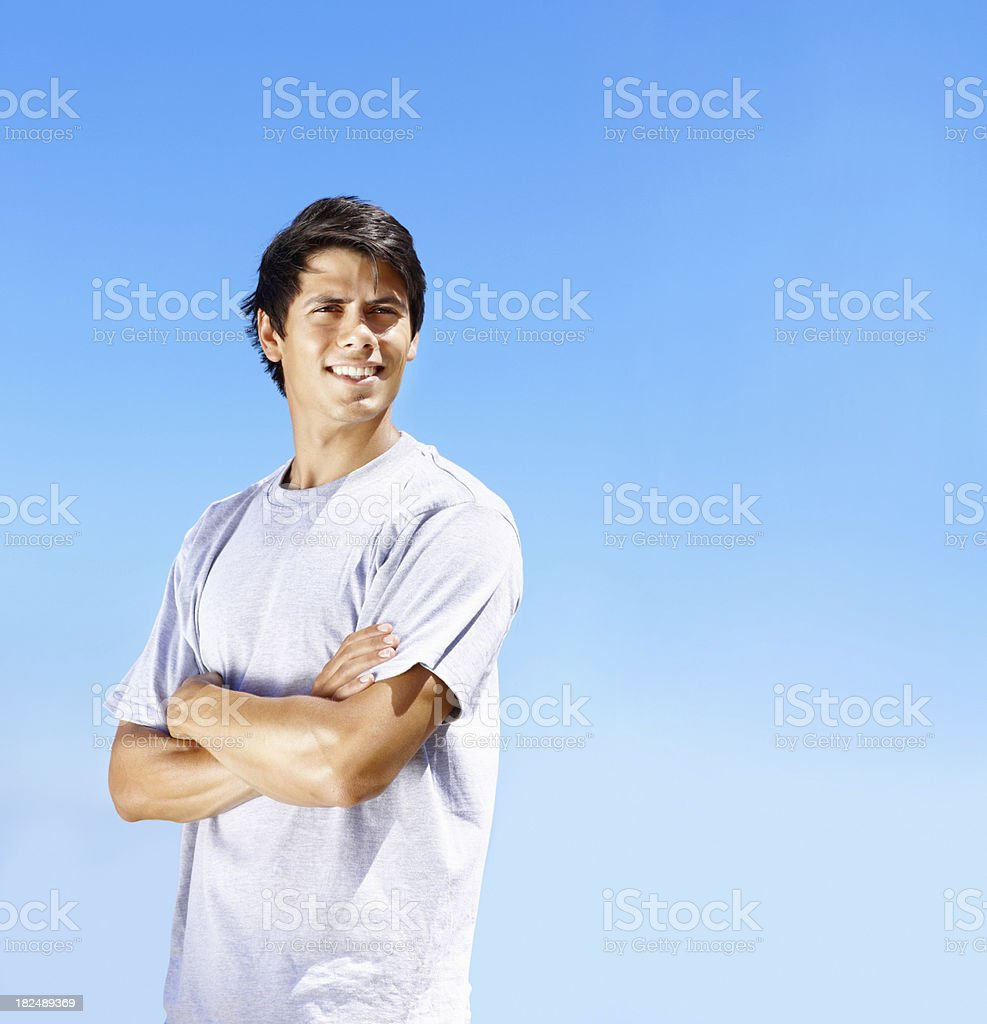 Smiling young guy with arms crossed against clear sky royalty-free stock photo