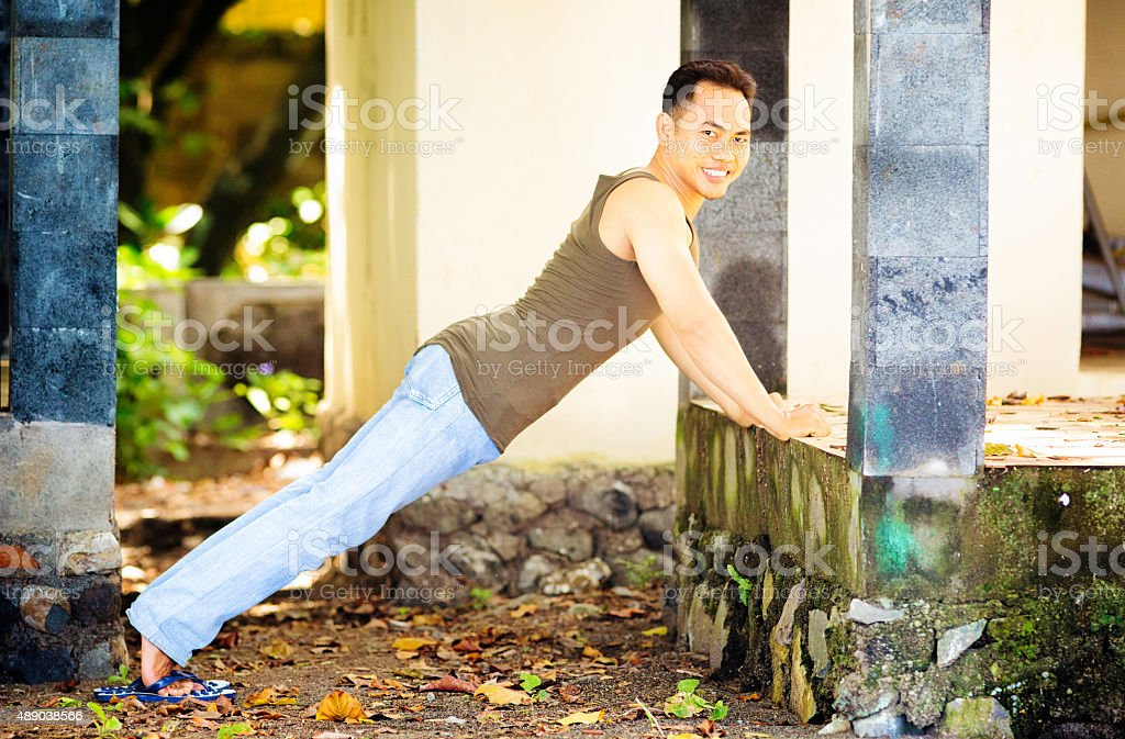 Smiling young Indonesian man surprised while doing push-ups stock photo
