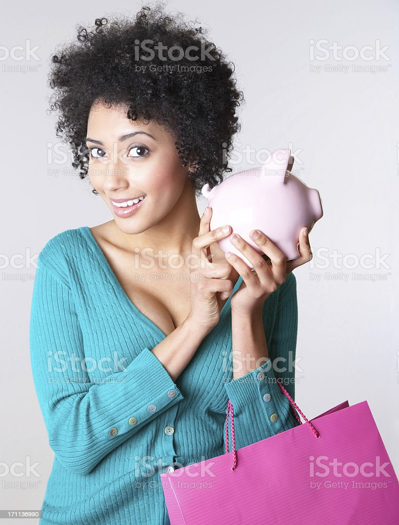 Smiling young lady holding piggy bank and shopping bag royalty-free stock photo