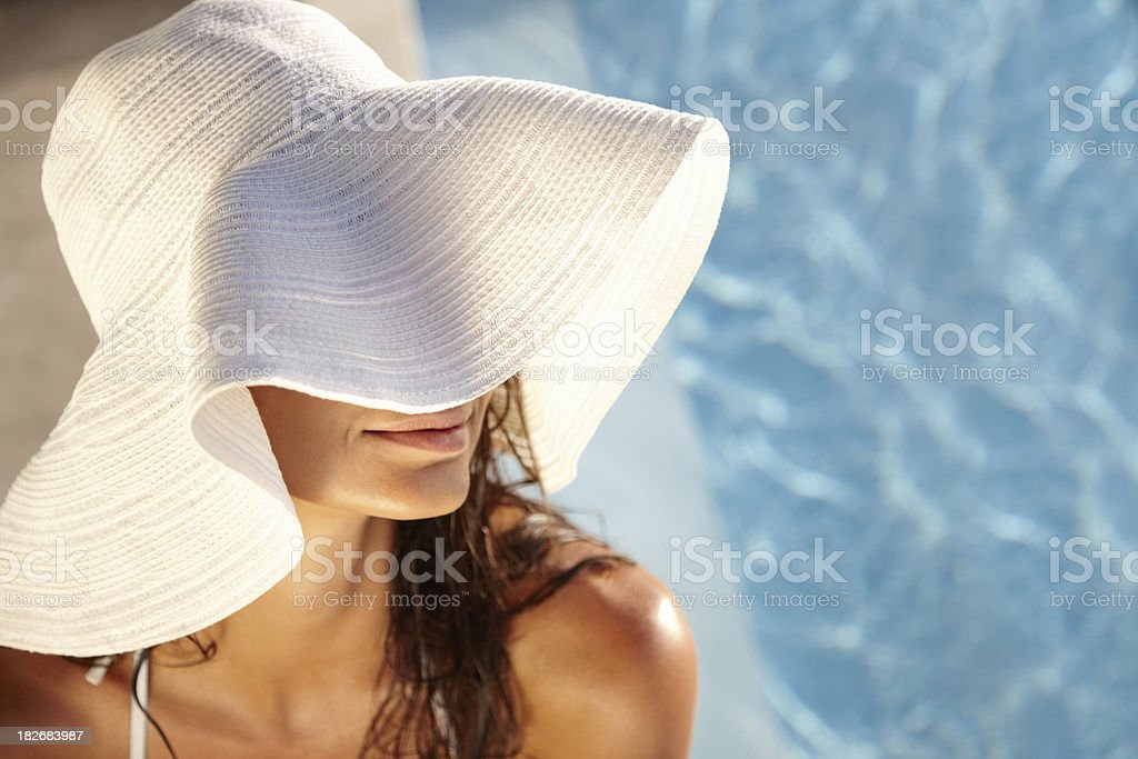Smiling young lady relaxing by swimming pool royalty-free stock photo