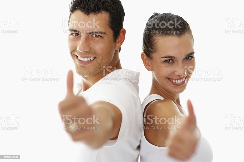 Smiling young man and woman giving a thumbs-up stock photo
