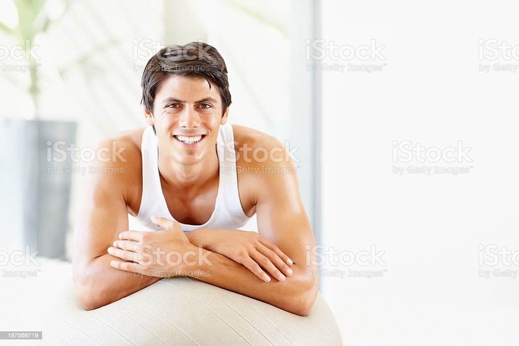 Smiling young man atop a fitness ball royalty-free stock photo