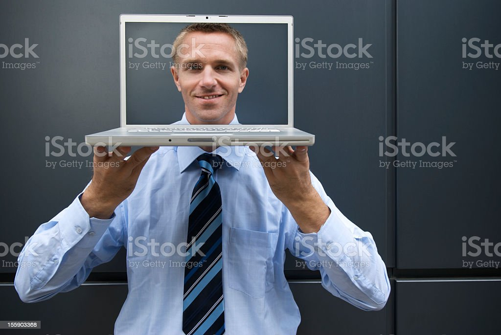 Smiling Young Man Businessman Holding Laptop with Face on Screen stock photo