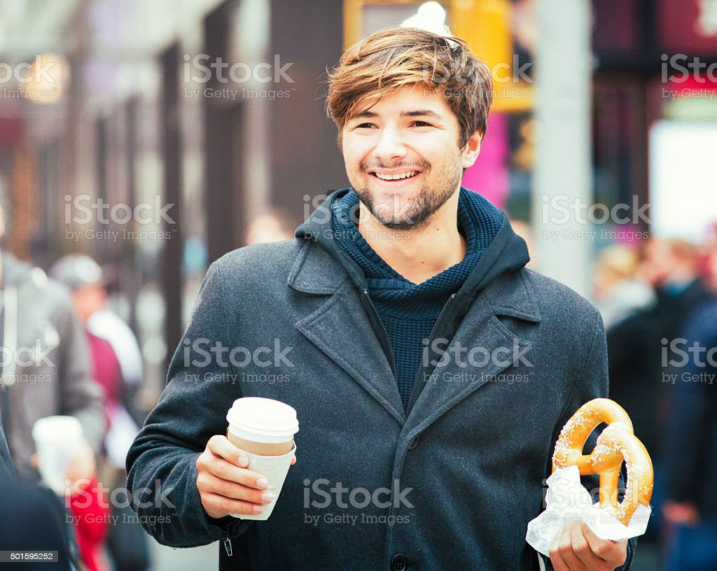 Smiling young man crossing Manhattan street with coffee and pretzel stock photo