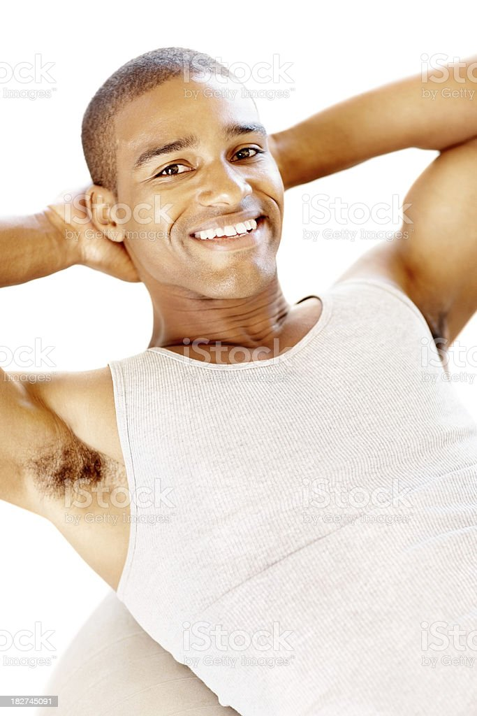 Smiling young man exercising on a fitness ball royalty-free stock photo