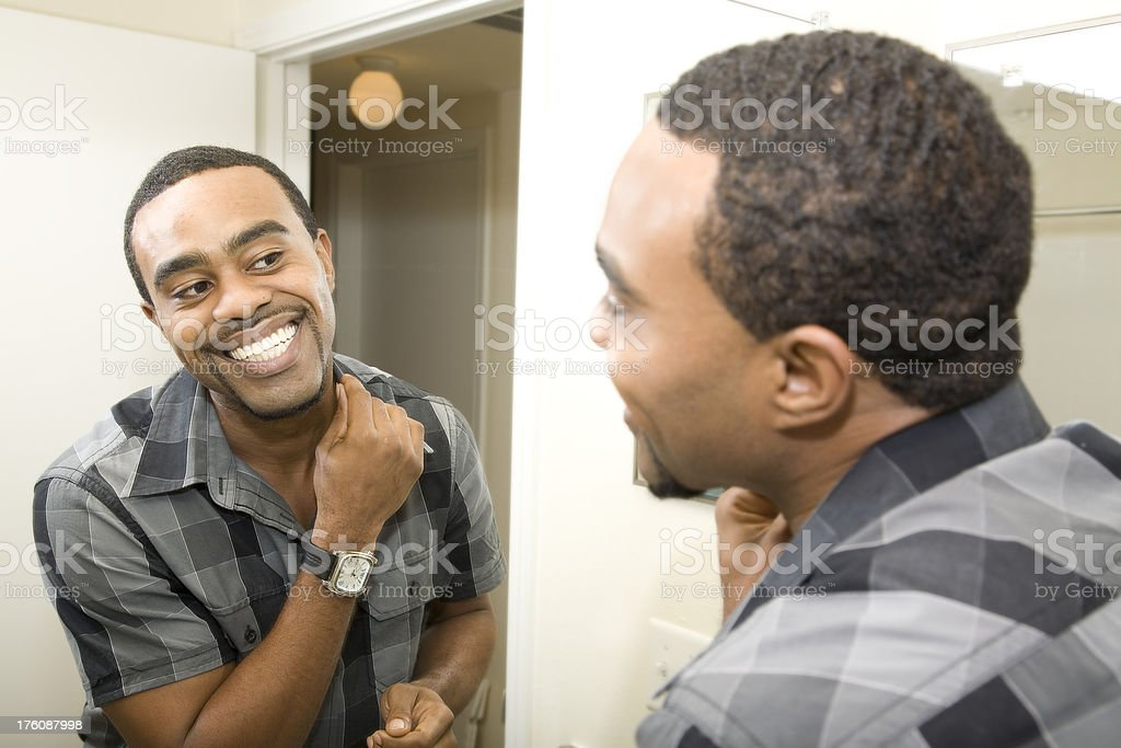 Smiling Young Man Getting Ready in front of Bathroom Mirror royalty-free stock photo