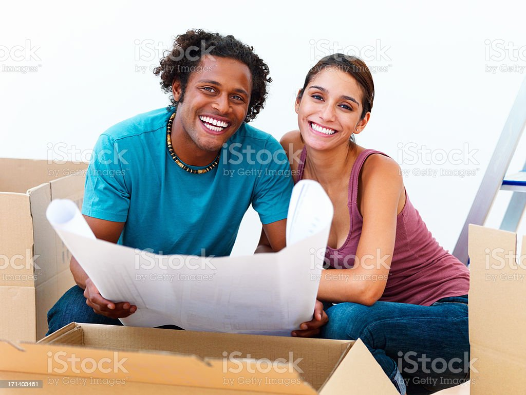 Smiling young man holding a blueprint by his girlfriend stock photo