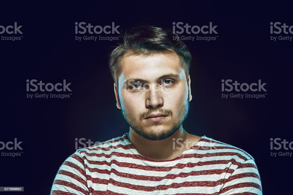 Smiling young man in striped tshirt looking up against stock photo