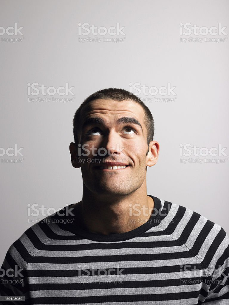 Smiling Young Man In Striped Tshirt Looking Up stock photo