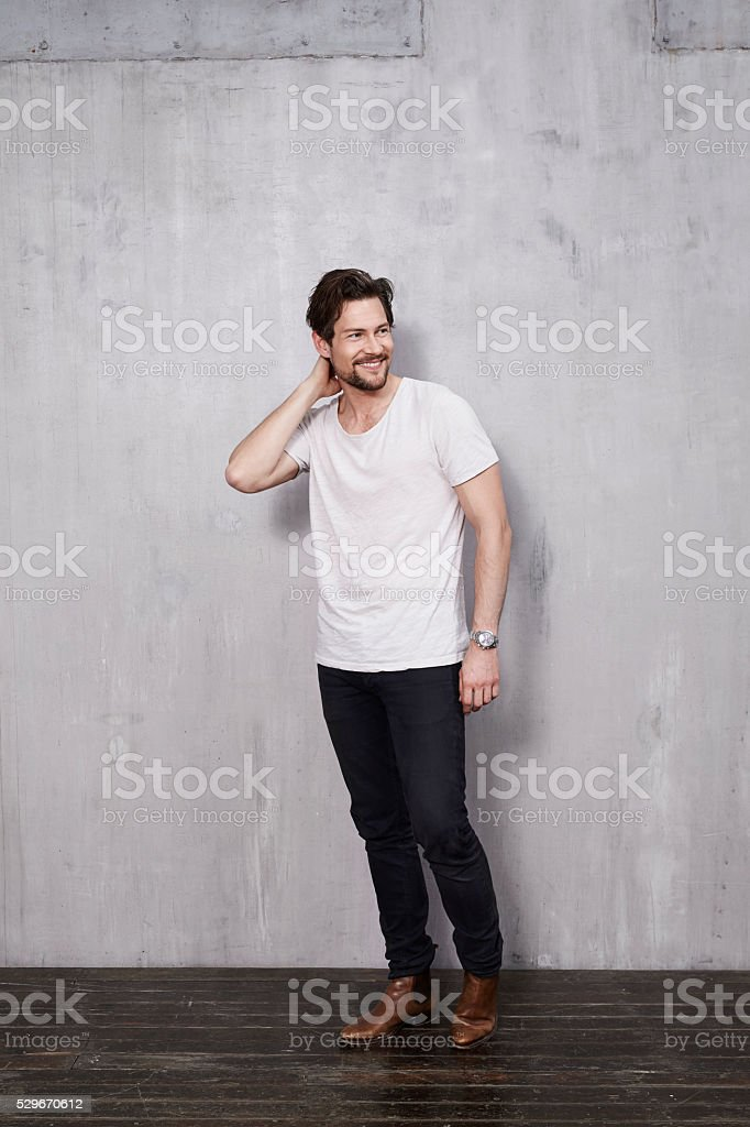 Smiling young man in studio, looking away stock photo