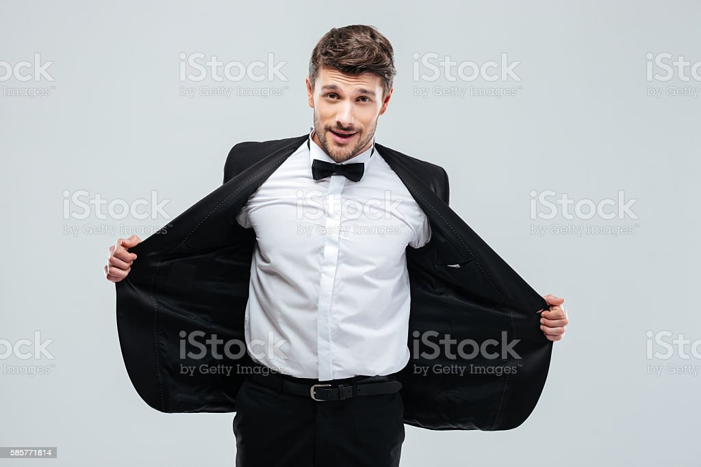 Smiling young man in tuxedo taking off his jacket stock photo