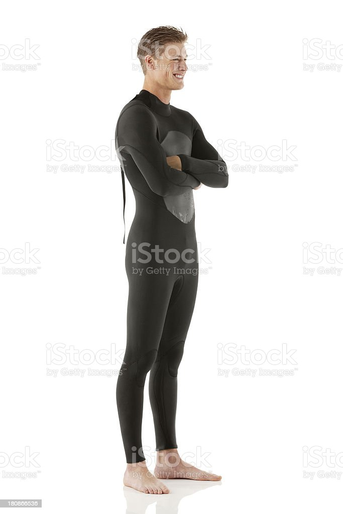 Smiling young man in wetsuit with arms crossed royalty-free stock photo