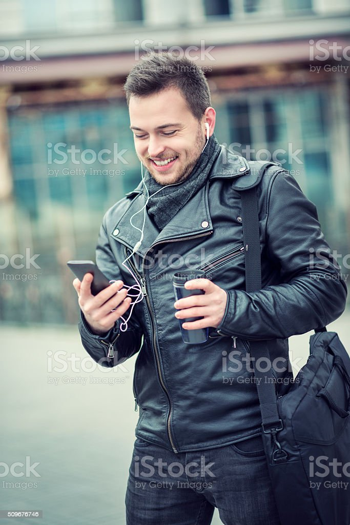 Smiling Young Man Listening Music and Drinking Coffee Outdoors stock photo