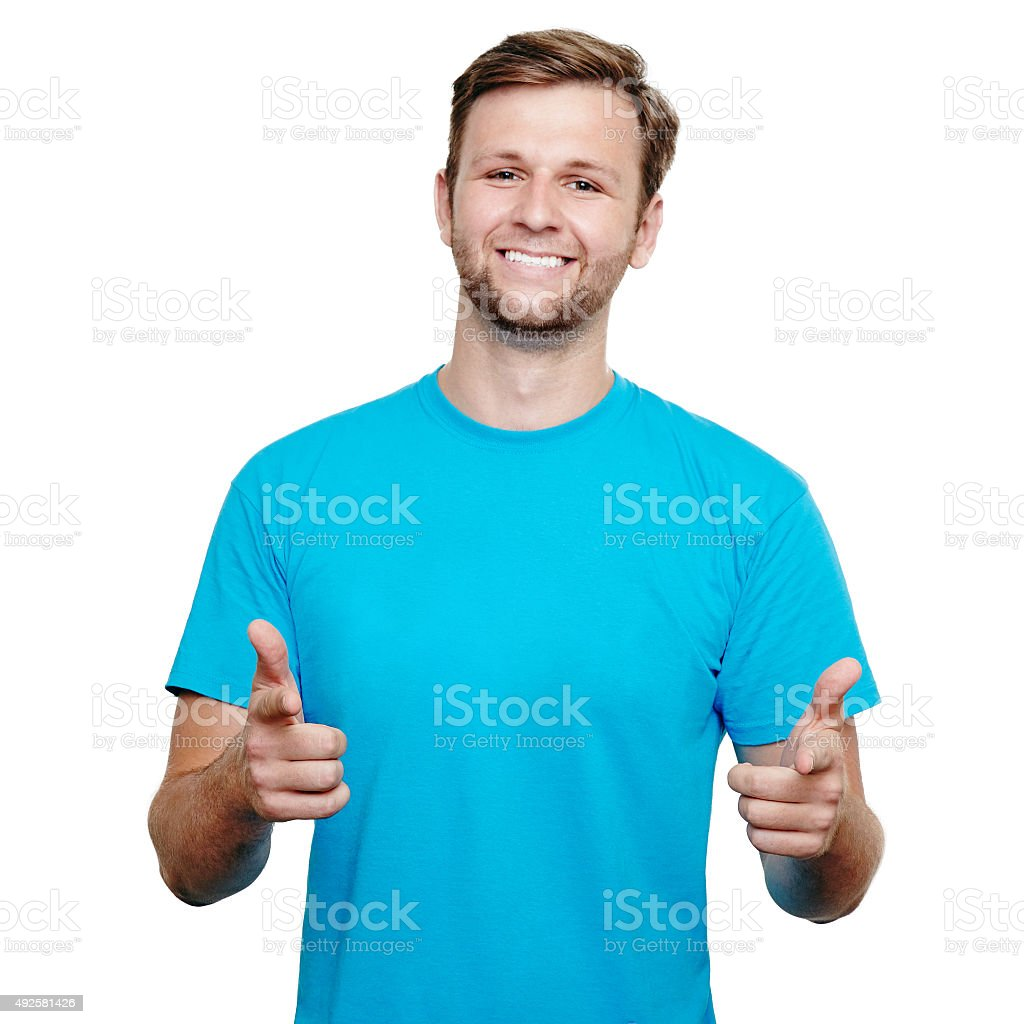 Smiling young man pointing at camera stock photo