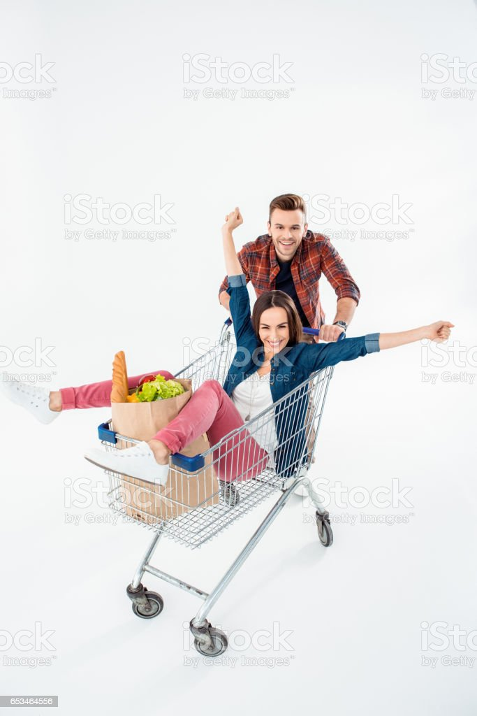 Smiling young man pushing shopping cart with excited young woman and grocery bag stock photo