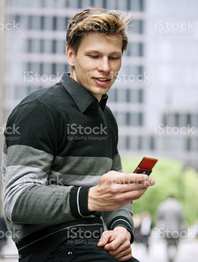 Smiling Young man reading SMS message on his mobile phone royalty-free stock photo