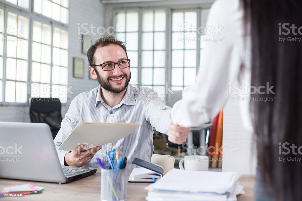 Smiling young man recieves documents at the office stock photo
