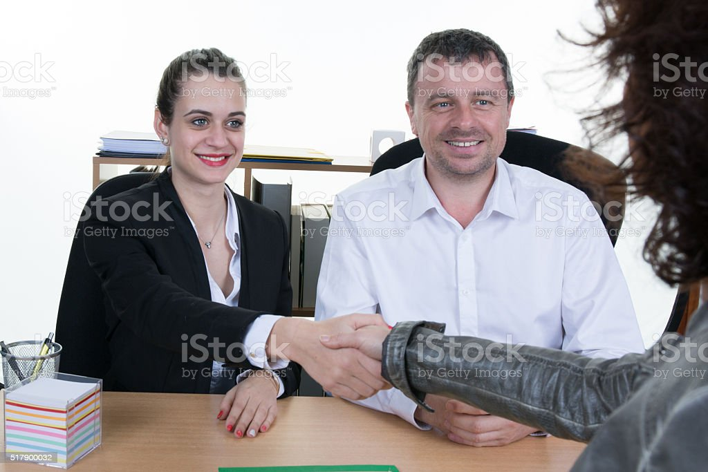 Smiling young man shaking hands with an insurance agent stock photo
