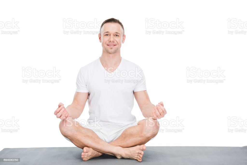 Smiling young man sitting in lotus position and looking at camera stock photo