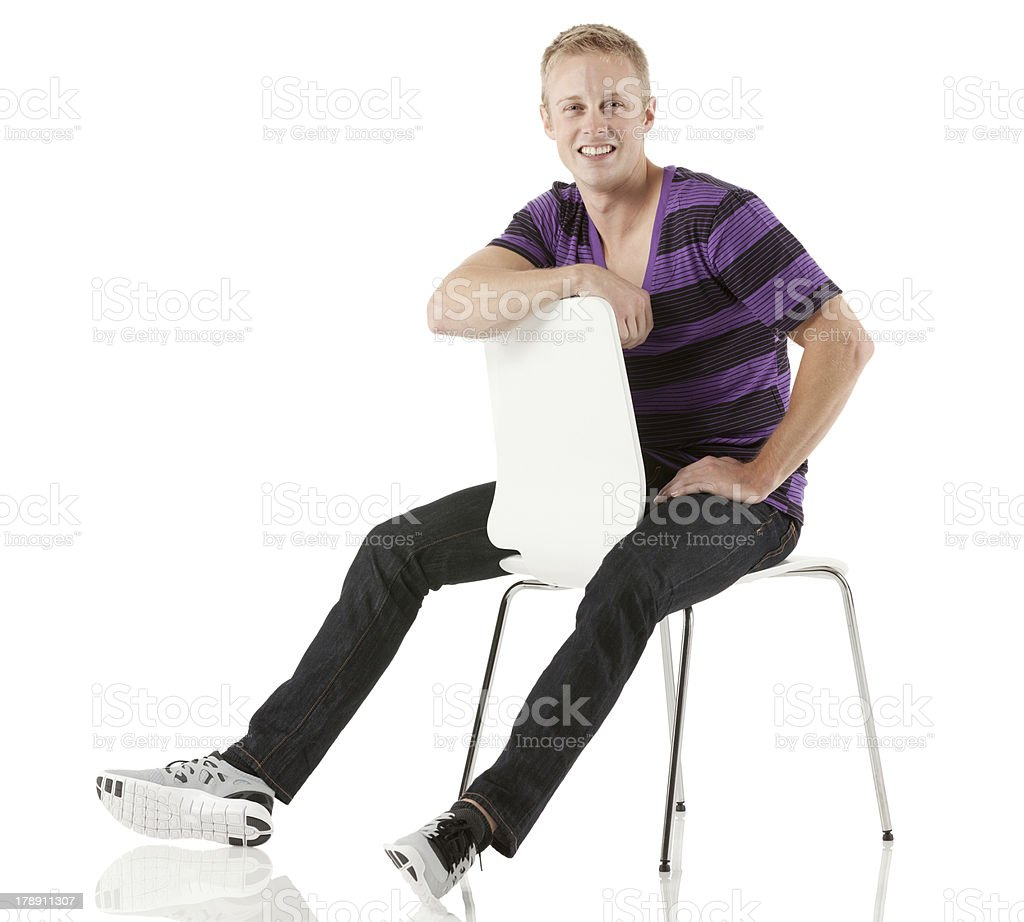 Smiling young man sitting on a chair stock photo