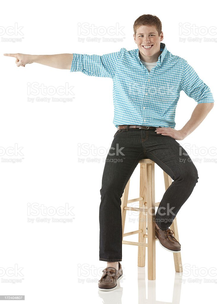 Smiling young man sitting on a stool and pointing royalty-free stock photo