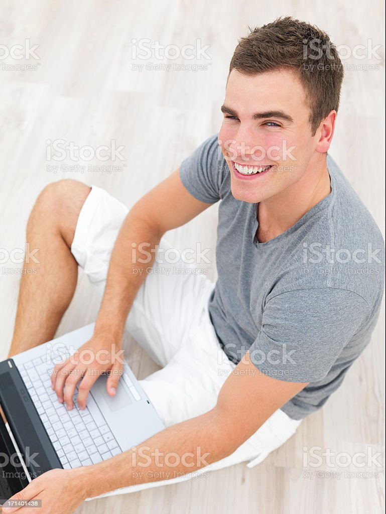Smiling young man sitting on floor using a laptop royalty-free stock photo