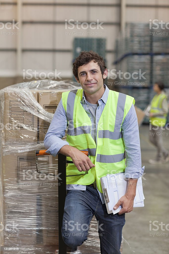 Smiling young man standing near cardboard box stock photo