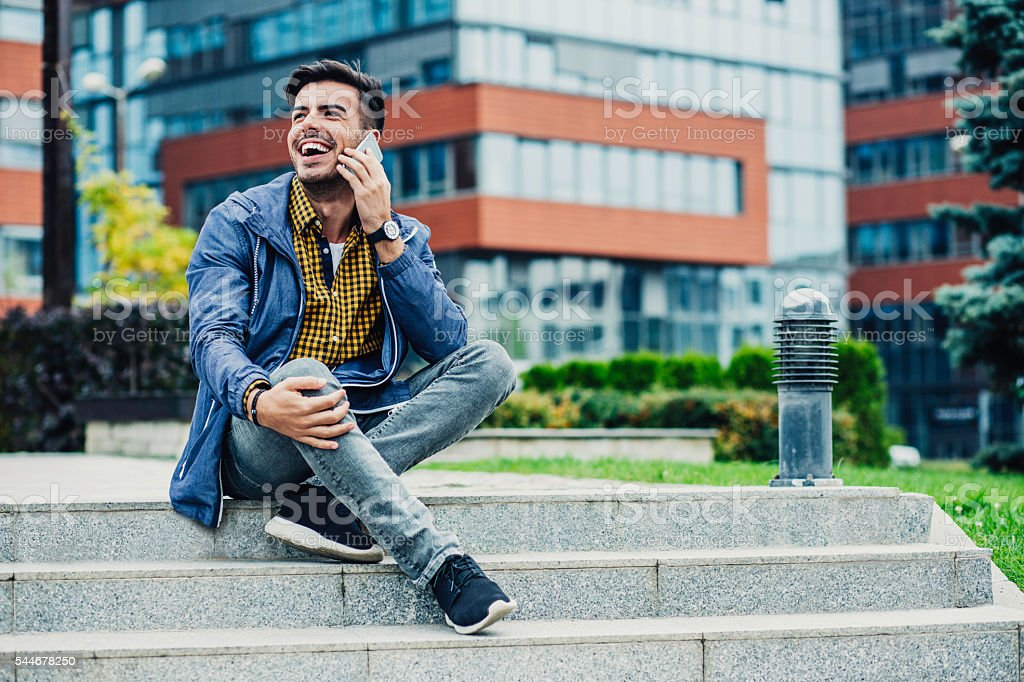 Smiling young man talking on the phone stock photo