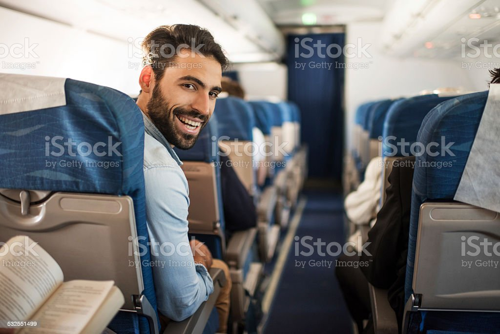 Smiling young man traveling by plane. stock photo