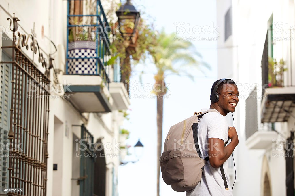 Smiling young man traveling with bag and headphones stock photo
