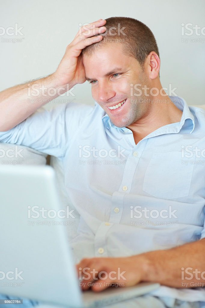Smiling young man using laptop at home royalty-free stock photo