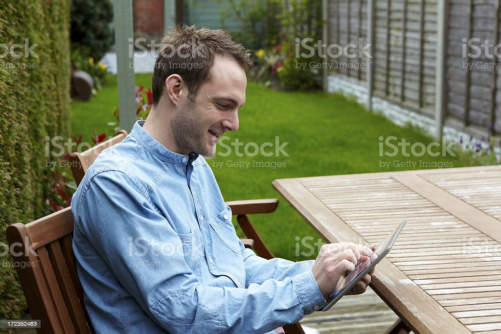 Smiling young man using tablet computer - Outdoors royalty-free stock photo