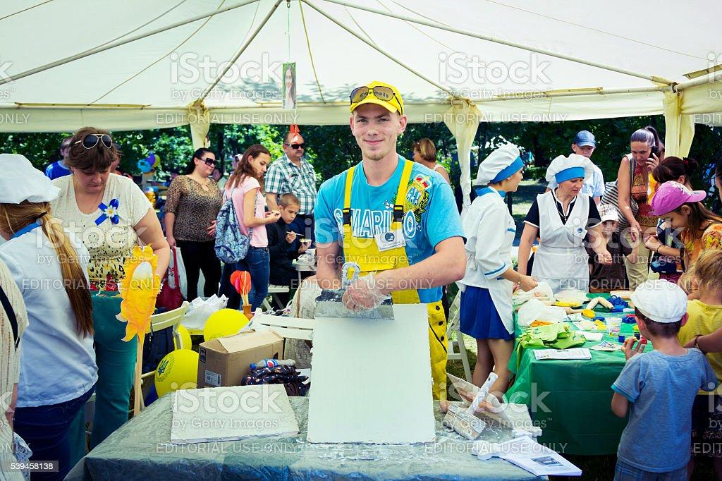 smiling young man volunteer presents plastering skills stock photo