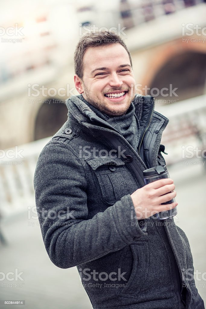 Smiling Young Man with Coffee in Hands on City Street stock photo