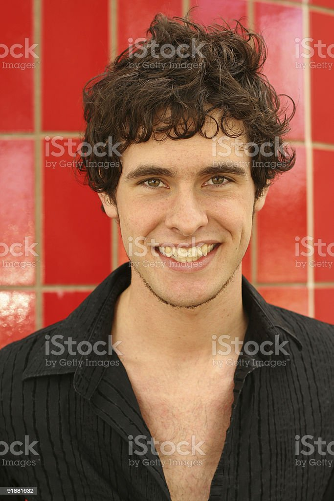 Smiling young man with curly hair on red background stock photo