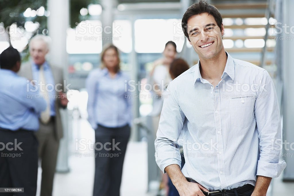 Smiling young man with his colleagues at the back royalty-free stock photo