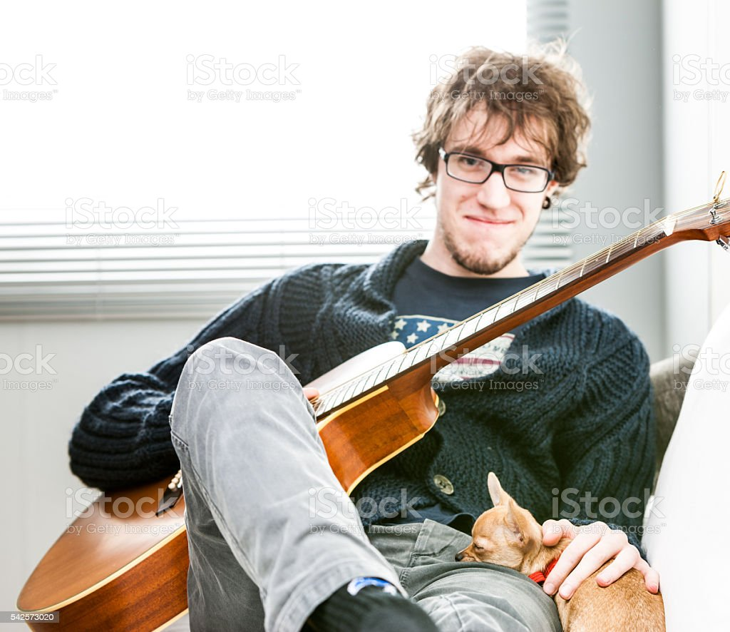 Smiling young man with his guitar and dog stock photo