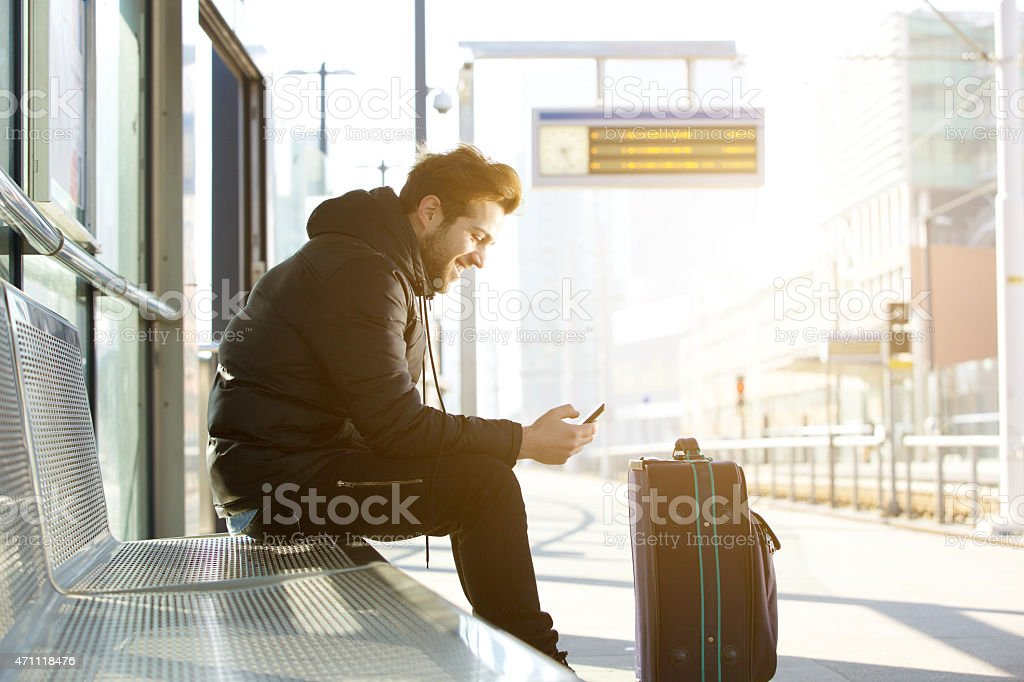 Smiling young man with mobile phone and bag stock photo