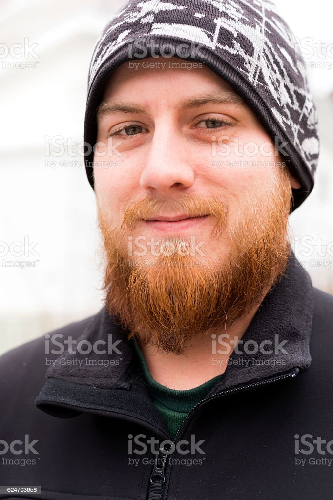 Smiling young man with red beard stock photo