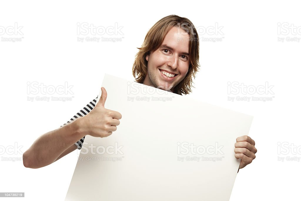 Smiling Young Man with Thumbs Up Holding Blank White Sign royalty-free stock photo