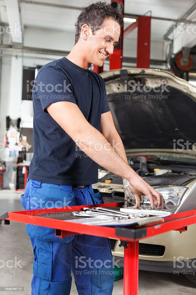 Smiling young mechanic working on a laptop royalty-free stock photo