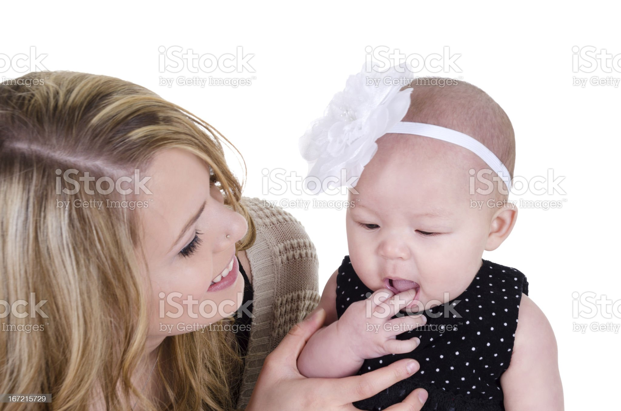 Smiling young mom holding baby playing with mouth. royalty-free stock photo